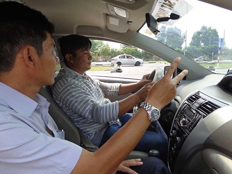 Giáo viên đang hướng dẫn học viên thao tác lái xe